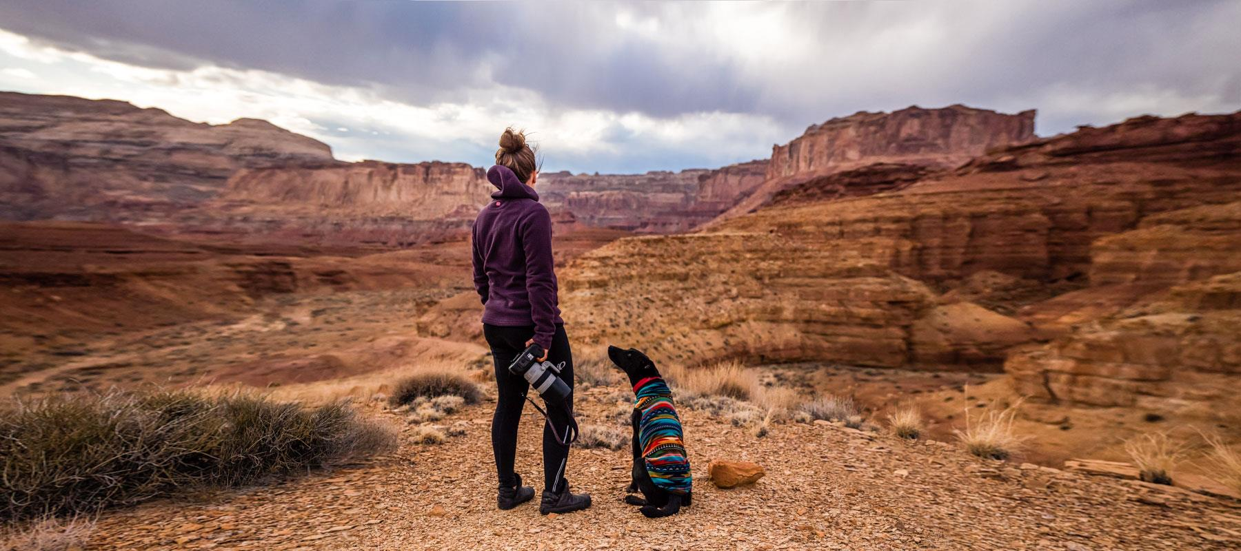 woman photographer hiking with dog san rafael swell utah